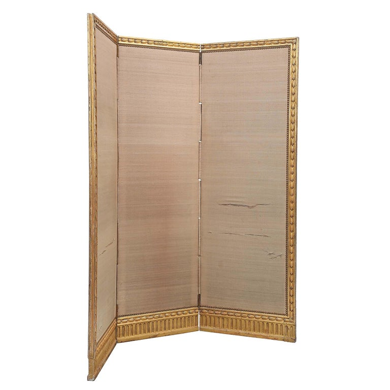 An elegant French mid-19th century giltwood Louis XVI st. three panel screen. The screen with all original gilt is decorated by carved wheat foliage while the bottom is finished by a fluted design below the wheat. The center of each panel is fitted