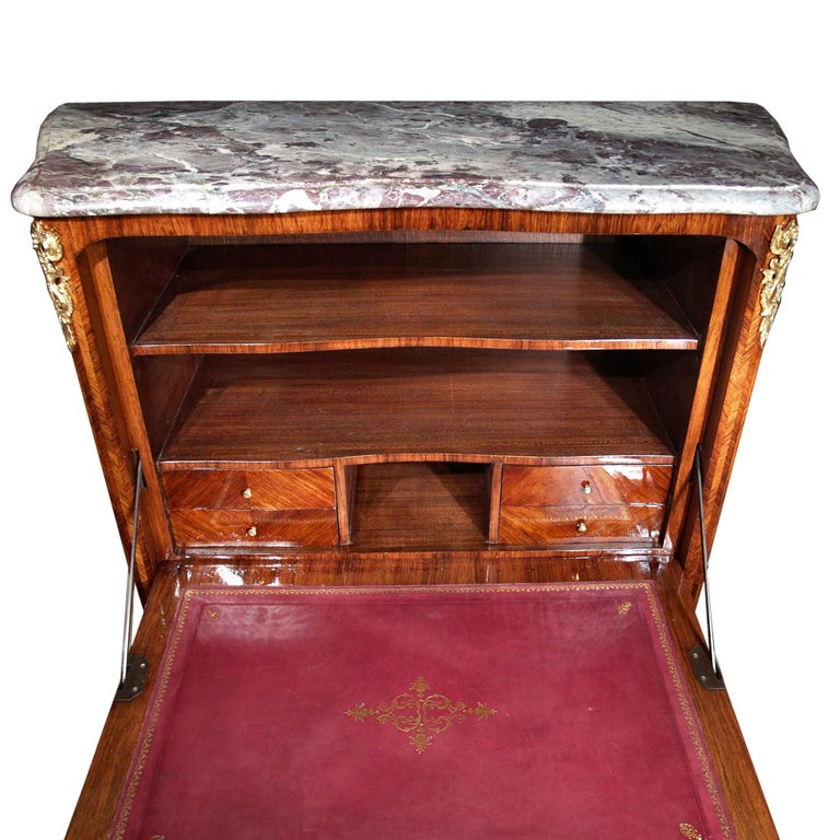 A French mid-19th century Louis XVI St. tulipwood secrétaire. The secrétaire has a fine quarter veneered tulipwood Marquetry on the front and sides, ornamented with pierced ormolu mounts. The bottom doors open to reveal in interior shelf. The drop