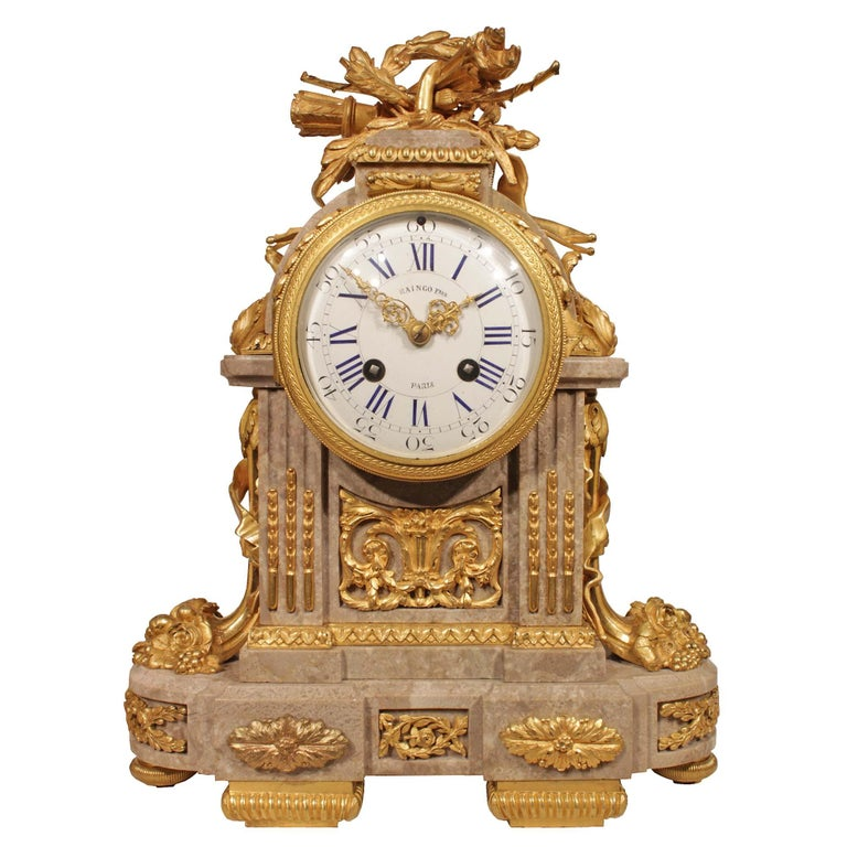 A sensational mid-19th century French Louis XVI style three-piece garniture set signed Raingo Frères, Paris. The clock with a brown and white vein color marble is highly decorated by ormolu mounts with all original gilt. The set has a pair of two
