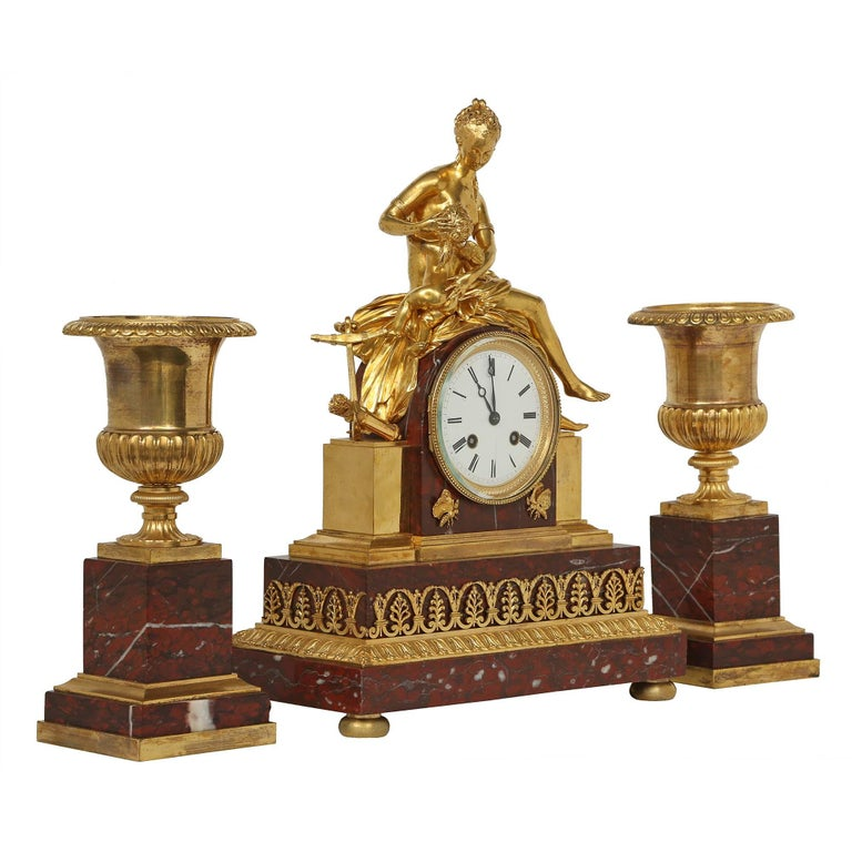 A very handsome three piece French mid 19th century Neo-Classical st. garniture set signed Japy Fréres (who won a gold metal for this clock in 1855). The clock is raised by a rectangular dark red marble base decorated by highly chased ormolu mounts