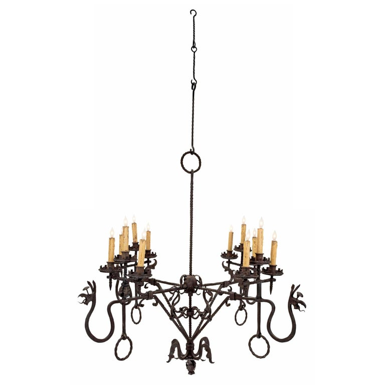 A very impressive and large scale French mid-19th century wrought iron twelve-light chandelier. An acanthus leaf bottom finial is below four twisted iron supports, decorated with scrolled serpents. Above each base are three candle cups with rook