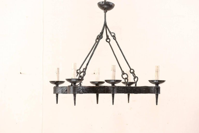 A French midcentury forged-iron six-light chandelier. This French vintage chandelier has an overall curvy, yet rectangular-shape. Six torch style lights, with iron cup style bobèches, are supported within the tightly scrolled arm extensions along