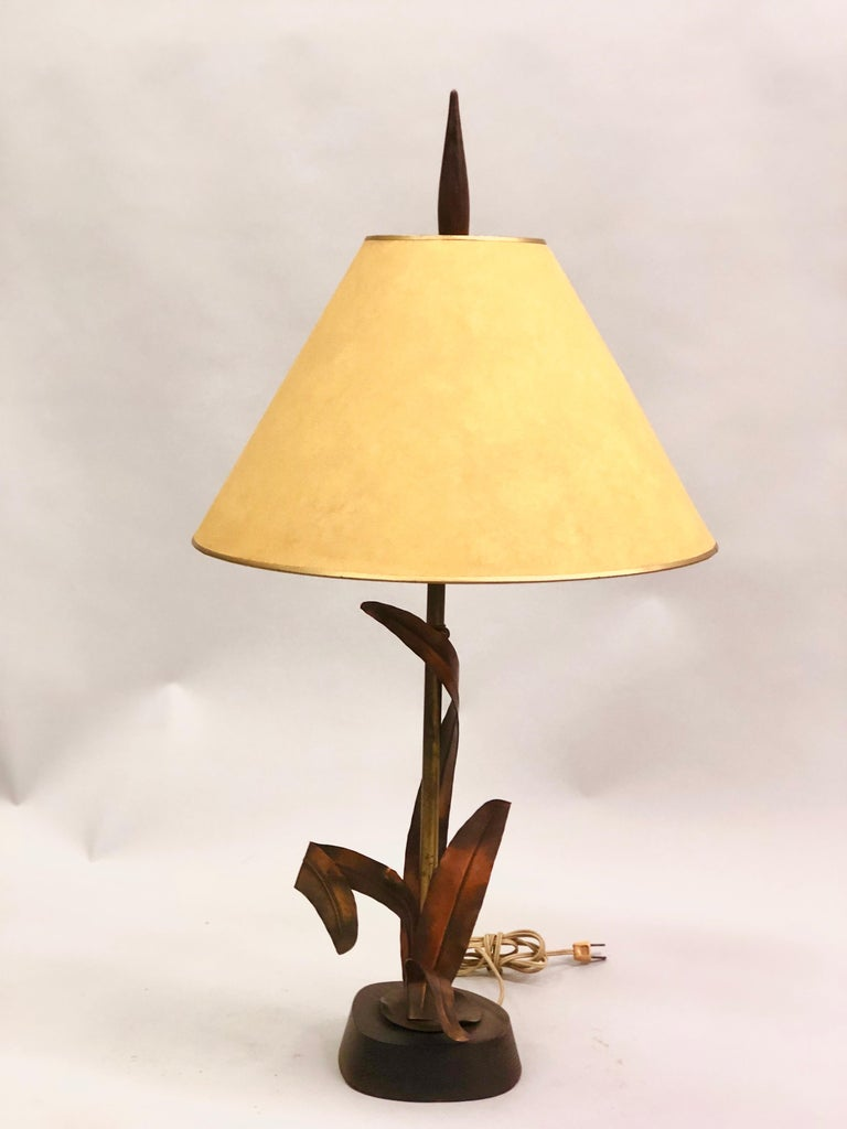 French Mid-Century Modern copper, bronze and brass floral table lamp by Maison Charles et Fils. The copper is elegantly formed to wraparound a brass stem. Base and tapered finial are composed of wood.   Measures: Diameter of lamp itself is 8