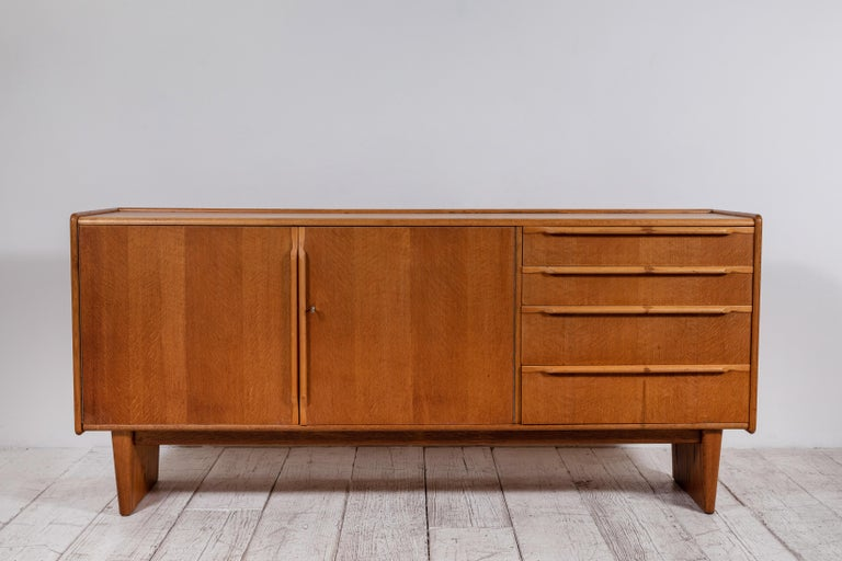 French midcentury credenza with four drawers and two doors. Beautiful wooden drawer pulls offer a tonal and modern look.