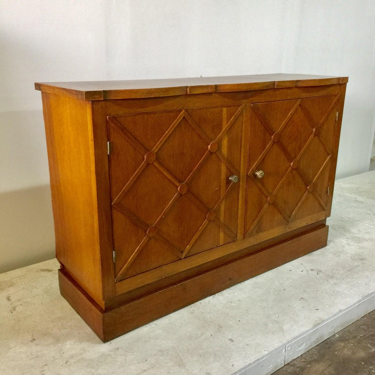 """This piece was customized for a specific commercial space in 1940s in the style of Jean Royère. 2 doors open to open shelving. The sides of this cabinet are being left """"as found"""" which was likely inserted in to a niche space. This is all oak. Note:"""