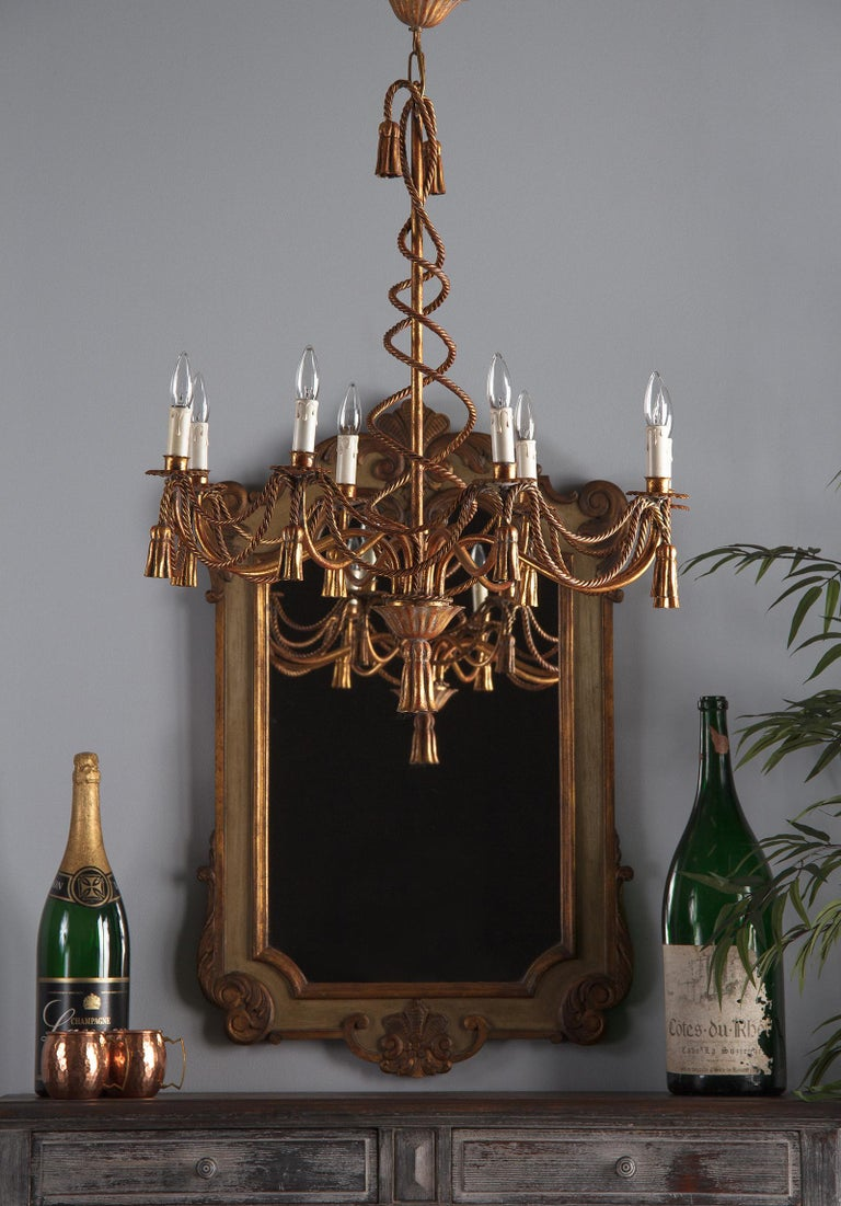 A gorgeous vintage gilt metal eight-light Louis XVI style chandelier, French midcentury. Eight undulating arms reach out from a centre post, each with a scalloped cup holding a faux candle light. Draping between each of the lights are two twisted