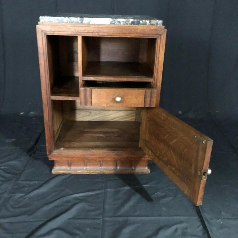 Wonderful oak midcentury French Art Deco side table or nightstand having one drawer and two open sections for books and sundries. Handsome thick marble top. #5201.