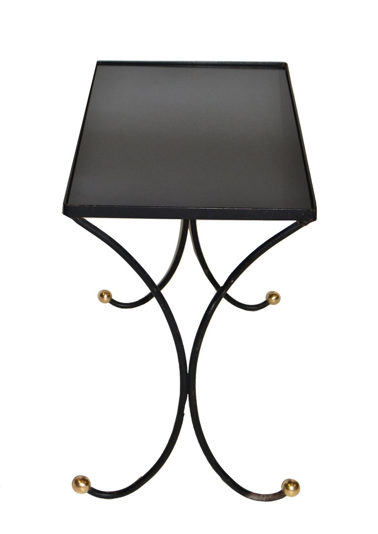 We offer this original 1950s ebonized wrought metal side table with round brass feet. features a black glass top. Is left in original condition with wear to the feet.