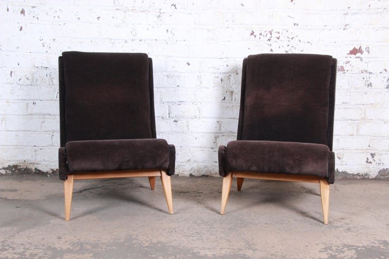 A gorgeous pair of French Mid-Century Modern low lounge chairs. The chairs feature sleek midcentury design, with tapered solid maple legs and angled seats and backs with brown velvet upholstery. Made in France, circa 1950. The chairs are in very