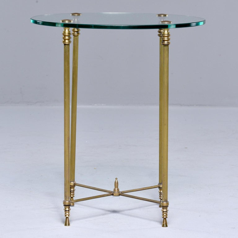 Small round side table found in France, circa 1960s. Round glass tabletop, x-form brass stretchers with a center finial and reeded brass legs. Unknown maker.