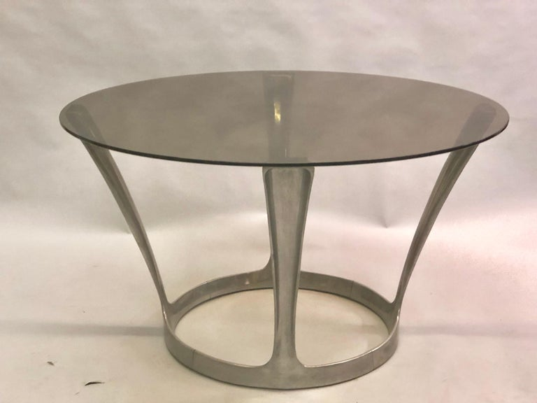 French Mid-Century Modern round center or dining table with a cast aluminum base and a smoked glass top by Boris Tabacoff circa 1960.  We can polish the aluminum base to perfection.