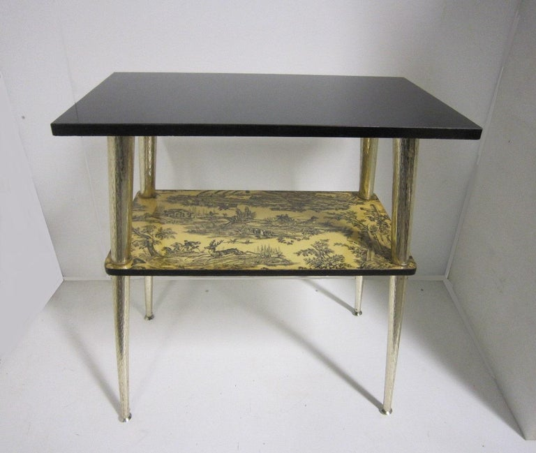 A French midcentury console table featuring a black top with toile patterns of a hunting scene on second tier; the whole raised on slender tapering satin nickel metal legs. The stretcher shelf is inspired by Toile, a French word meaning