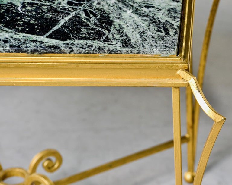 French marble-top coffee table with gilded iron frame, circa 1970s. Frame has fancy winged corners and supports with decorative scrolls. Marble-top is deep green with lighter green streaks and has no cracks, chips or repairs. Unknown maker.  Size: