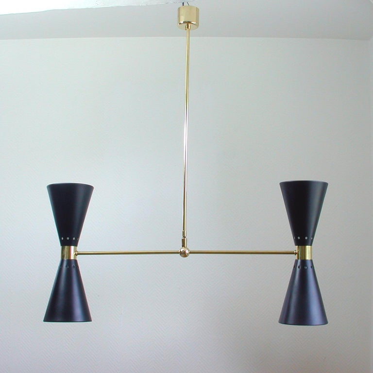 This elegant double cone chandelier was manufactured in France in the 1950s. It is made of brass and has got two black painted aluminum up and down diabolo shades.