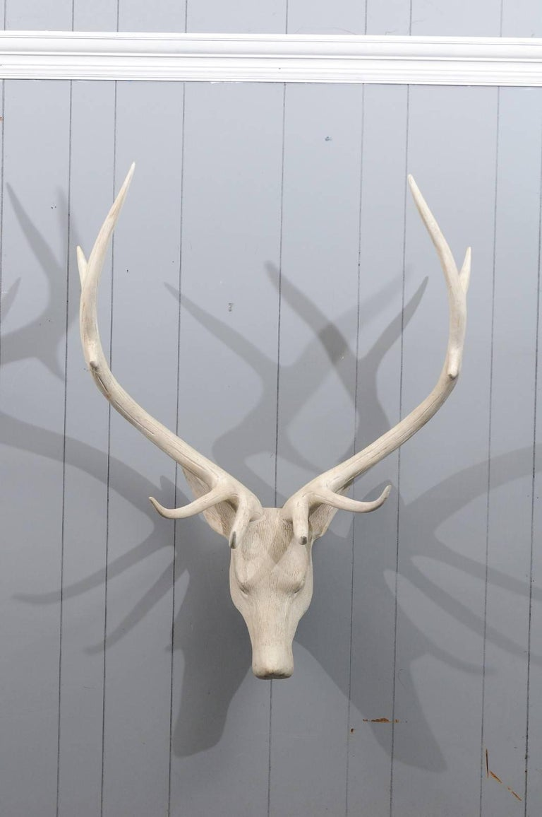 A French carved and painted wood deer head sculpture from the mid-20th century, with large antlers. This French deer head sculpture exudes a striking presence. The nicely detailed surface along with the expressive face are perfectly emphasized by