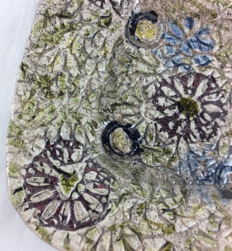 A handsome midcentury French decorative plate or large vide poche. The apparent very talented ceramist used textures that resemble that of a painting of flowers. The wonderful form and colors on the beige background reflect the artist's painterly