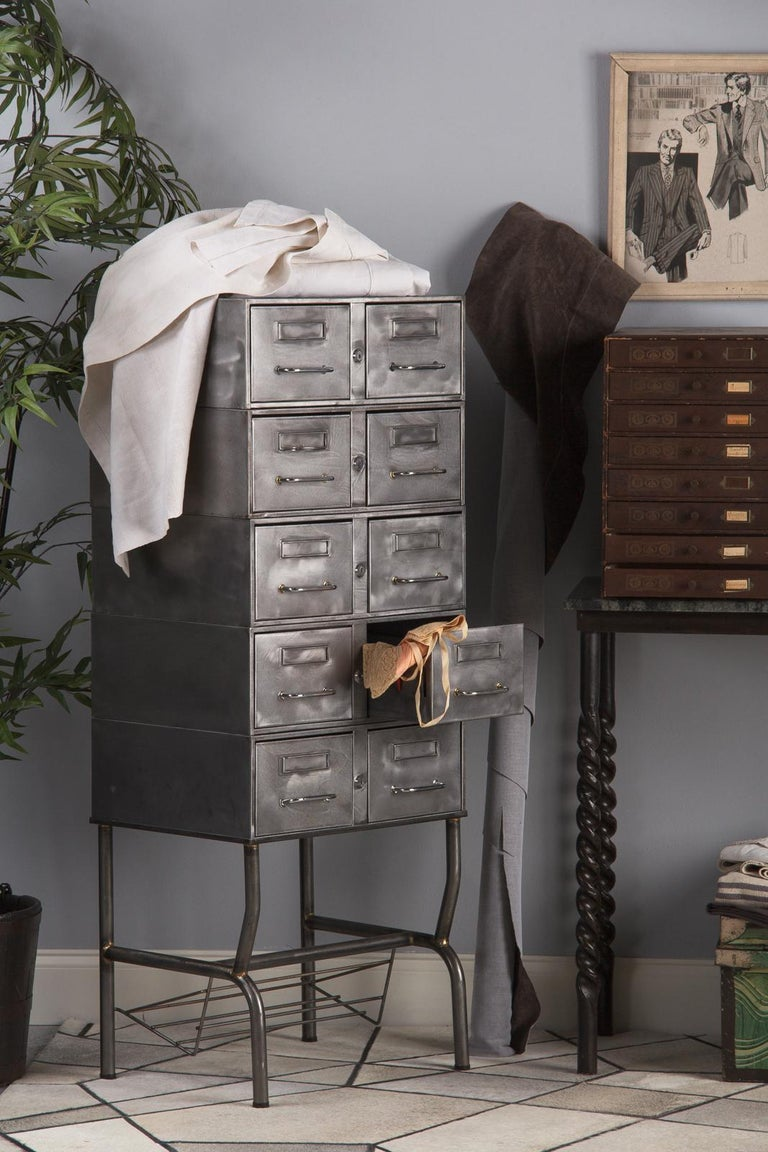 A tall Industrial polished steel file cabinet on an open base, French midcentury. Ten drawers in two columns are housed in a handsome polished steel case perched over a four legged base with a wire shelf built in. The cabinet is in three parts, with