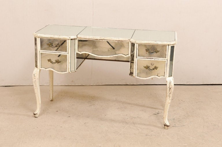 A French midcentury mirrored dressing table. This beautiful French vanity is adorned in a mirrored exterior, with sweetly designed lines, canted side posts, accented with old white paint, and presented upon slender cabriole legs with acanthus