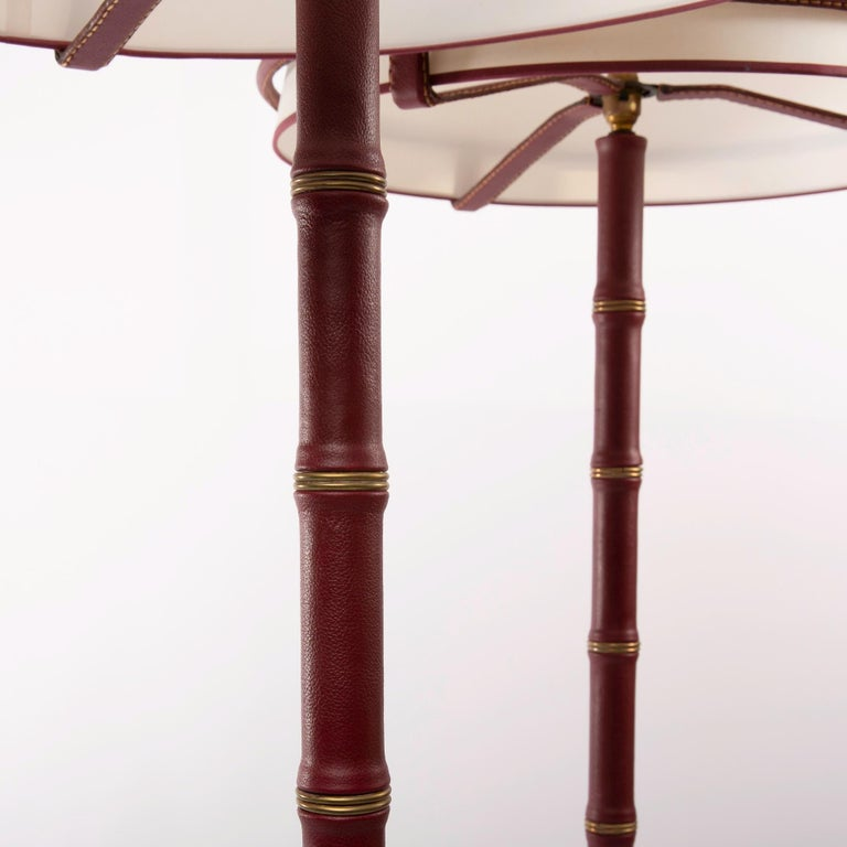 A fine pair of floor lamps designed by Jacques Adnet and manufactured by Compagnie des Arts Français. The structure of theses lamps are made of steel and covered with saddle stitched burgundy leather. The lampshades are simply placed on the
