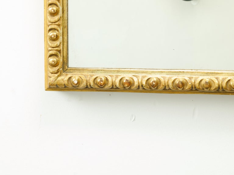 A French giltwood rectangular mirror from the mid-20th century, with carved ovoid motifs. Created in France during the midcentury period, this rectangular mirror features a carved giltwood frame adorned with a regular rhythm of ovoid motifs