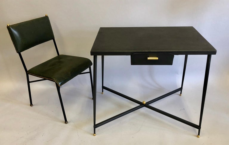 Sober, elegant, French modern Neoclassical desk or writing table in handwrought iron with iron pencil drawer and brass drawer pull.  The piece features four elegantly gently tapering legs that terminate in gilt ball feet and are united by X-form