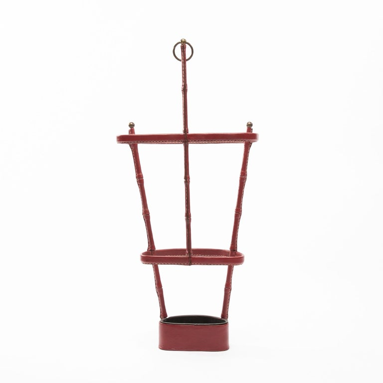 Very nice umbrella stand designed by Jacques Adnet and manufactured by the company of the French arts. Steel structure entirely covered with burgundy saddle stitch leather. Brass handle.  Jacques Edouard Jules Adnet was born in Châtillon-Coligny