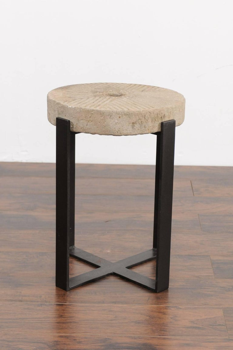 An old French millstone drink table mounted on a new custom-made iron base. We currently have two tables available, priced and sold individually. This charming drink table features an old early 20th century millstone top, adorned with the typical