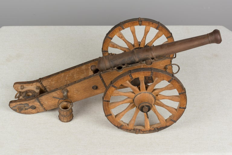 A French miniature model cannon made of iron with wood frame and trimmed in steel with rivets. In good condition with some water damage to wheels and rusty patina to iron. There is a missing bracket underneath that holds one of the wheels. Diameter