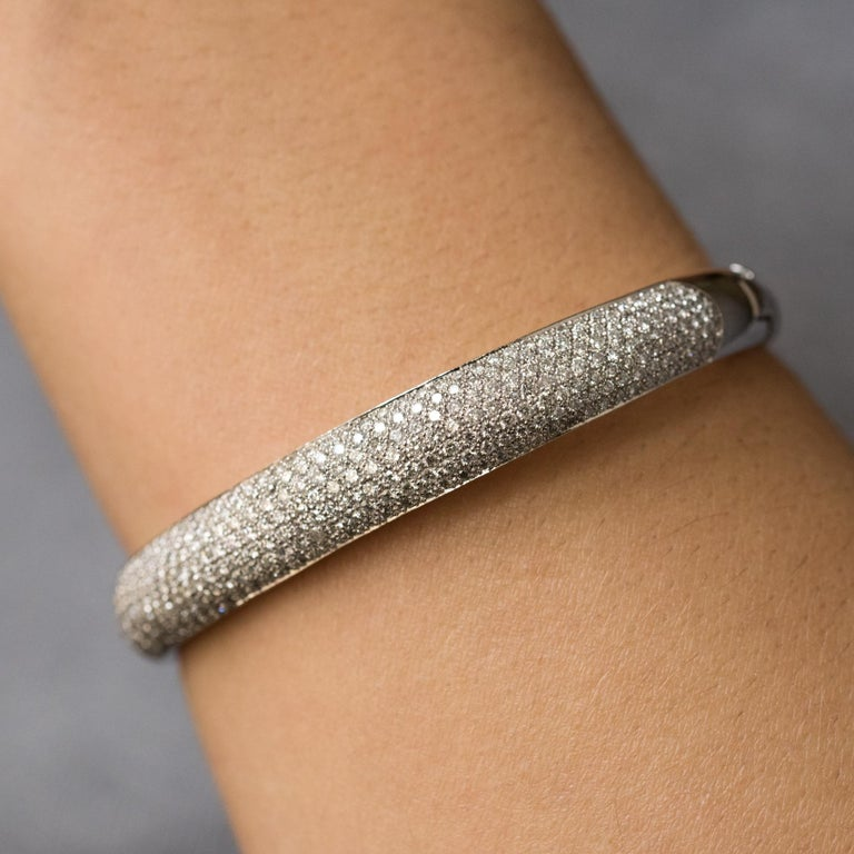 Bracelet in 18 karats white gold, eagle's head hallmark. Bangle shape, oval, it is paved with diamonds on its top. It is opening on one side by a hinge, the interior is perforated. The clasp is a ratchet with a diamond set on the thumb