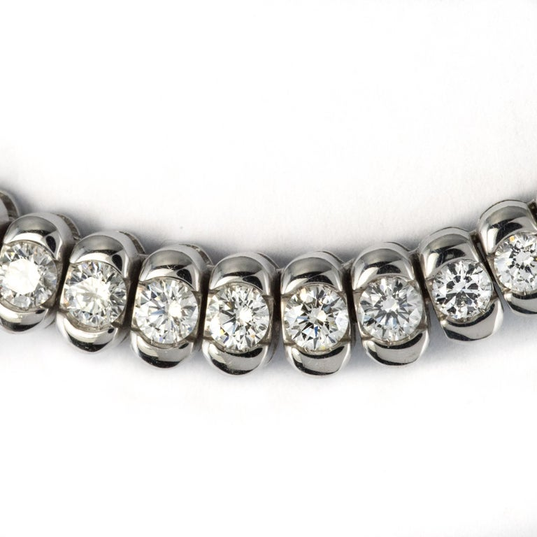 Necklace in 18 karats white gold, eagle's head hallmark. This modern necklace is made up of a series of polished gadroons in slight fall, the front of which is entirely set with 59 brilliant-cut diamonds. The clasp is ratchet with 8 security. Total