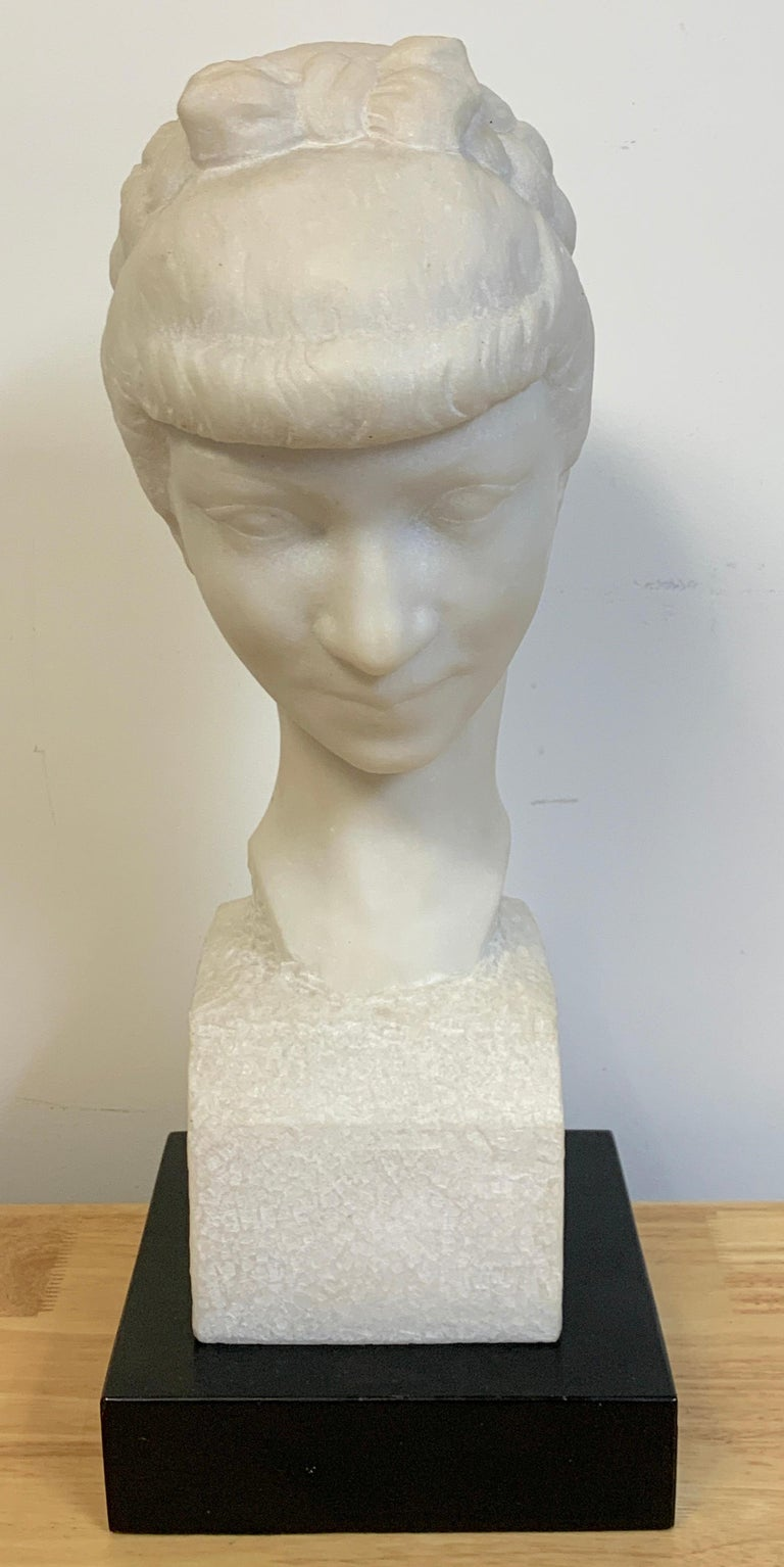 French modern marble portrait bust of a lady, by L. Cordonnier, '51  A serene carved marble portrait bust of a young lady with braided hair looking downwards. Signed L. Cordonnier, middle right Included is a later ebonized wood plinth Bust alone