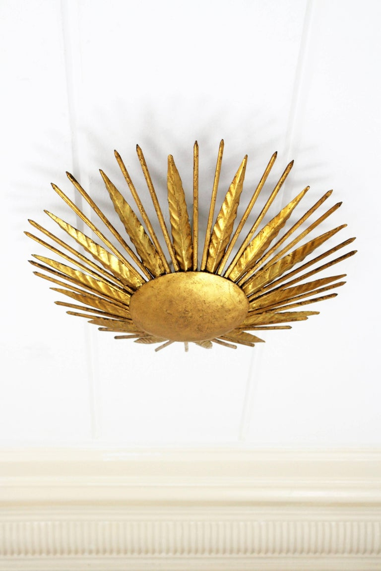 Hand-hammered gold leaf gilt iron sunburst light fixture from the late Art Deco period, France, 1940s. This piece is highly decorative due to its design, alternating iron leaves with pointed spikes. This light fixture can be hung as a wall or