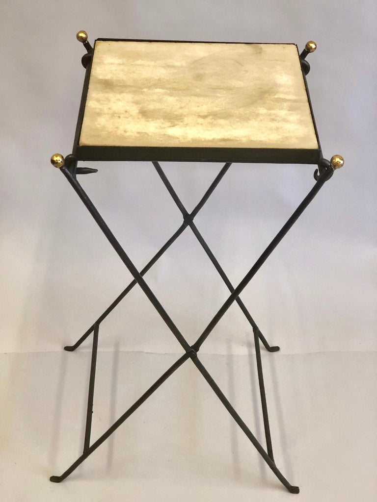 Elegant and unique French midcentury partially gilt wrought iron and marble folding side table or gueridon in the manner of Jean Michel Frank, circa 1935.  Though the folding 'campaign' table is composed of hammered iron and stone it is light and