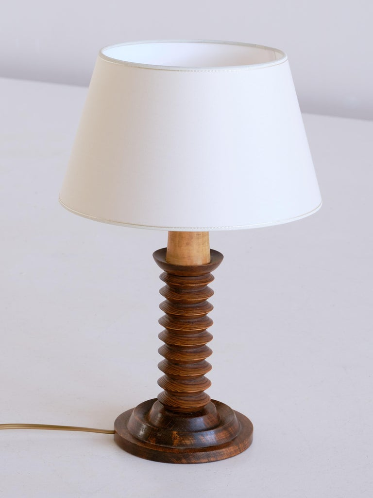 This rustic and elegant table lamp was produced in France in the 1950s. The lamp is made of dark stained oak wood and consists of a circular base and a carved stem in a stacked disc shape. The new ivory shade distributes a soft and pleasant light.