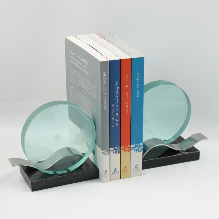 Architectural designed pair of bookends. Modernist shape build with large round disk glass slab with clouds and dot etching. Base in black granite and large chromed metal wave. Decorative, heavy and definitively usable as real bookends. No visible