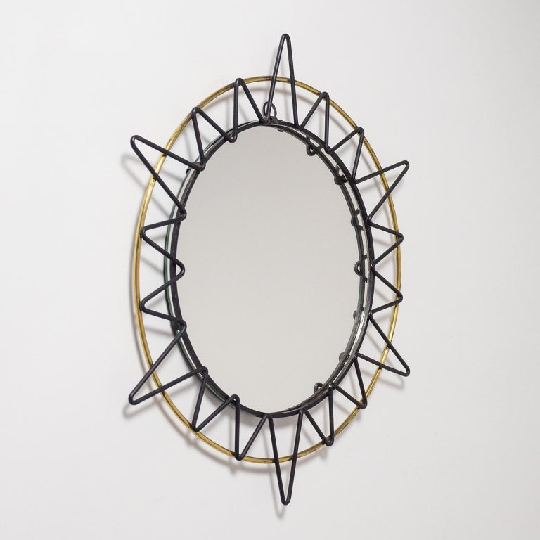Fine French artisanal sunburts mirror from the 1950s. A slim brass ring with black lacquered 'zig-zag' sun rays. Fine original condition with some patina on the brass and original lacquer. Mirror diameter is circa 10inches/26cm.