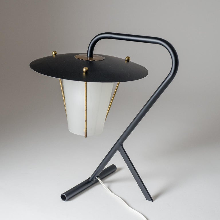 Brilliant modernist French table lamp from the early 1950s. The Minimalist sculptural base holds a lantern style body with glass diffuser (forsted on the inside). One brass and ceramic E14 socket with original switch and plug.