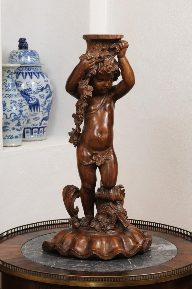A French Napoléon III period walnut carved putto sculpture from the mid 19th century, with grapes, flowers and the double flute. Created in France during the third quarter of the 19th century, this carved walnut sculpture depicts a putto draped with
