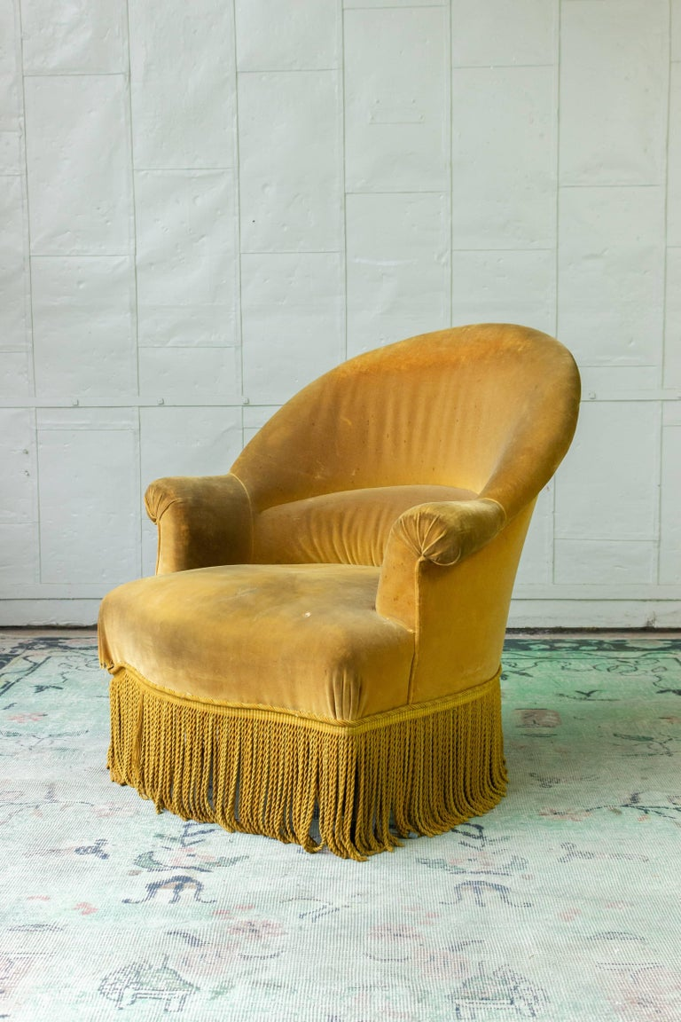 French 19th century armchair with a rounded back in gold velvet and bouillon fringe. The upholstery is not new and needs to be replaced. The chair is structurally sound and ready to be re upholstered.