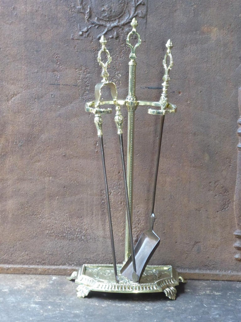 Stylish 19th-20th century French Napoleon III fireplace tool set. The fire irons consist of a stand and two fireplace tools. They are made of polished brass and wrought iron. The fire tools are in a good condition and are fully