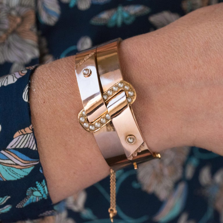 Bracelet in 18 karats rose gold, rhinoceros head hallmark. Oval shaped, this beautiful antique bracelet is made of 2 flat gold ribbons which go through a loop on the top set with natural half pearls. Each ribbon ends with 4 chiseled ends and is set