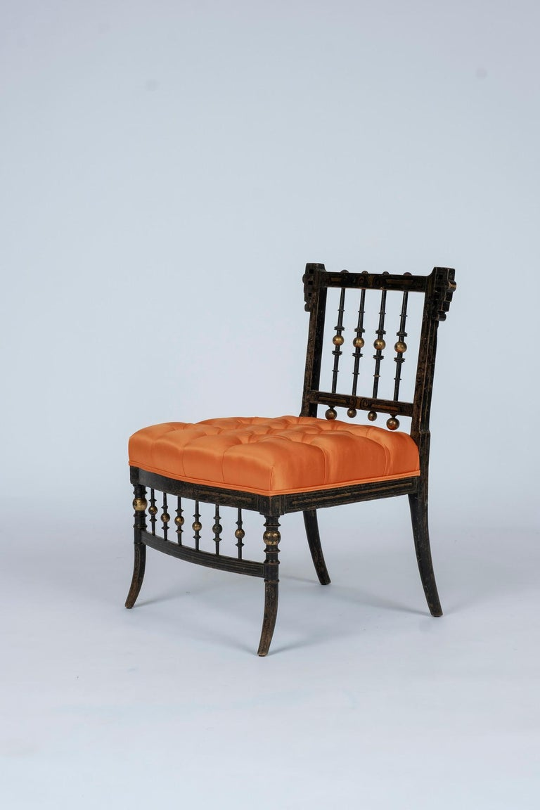 These low chairs were all of the rage in mid-19th century Paris. It's ebonized wood frame has been decorated with polychrome and parcel-gilt details and newly upholstered in a luxurious satin silk with button tufted detailing. A perfect chair to