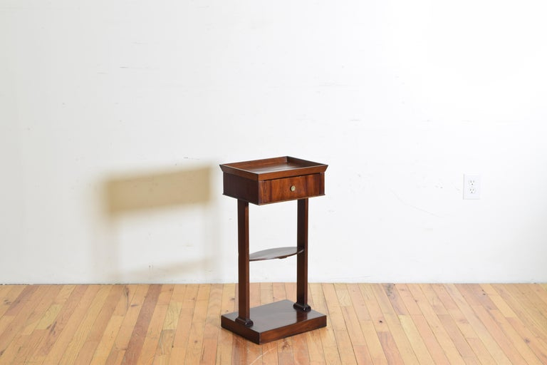 Somewhat diminuitive in size this table features a tray top with a two-way drawer raised on straight trestle legs joined in the middle by a flattened oval stretcher, the legs continuing to a square platform base, second quarter of the 19th century.