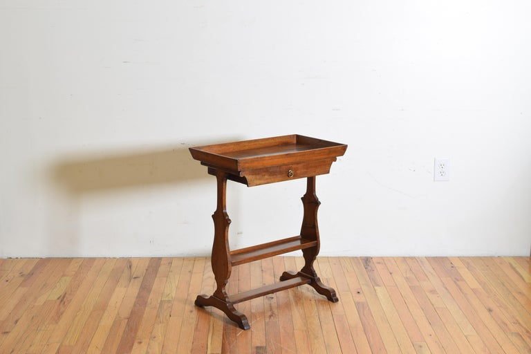 having a deep tray top above a single drawer, the shaped trestle legs joined by a centered tray with a small gallery edge, the bracket feet joined by yet another flattened stretcher, second quarter of the 19th century.