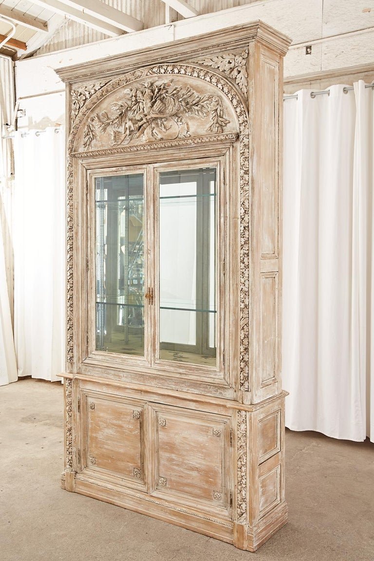 Magnificent French bookcase or display cabinet crafted in the neoclassical Louis XVI taste. The two-part case features extensive relief carved decoration with an oak foliate and acorn motif. Constructed from pine with a cerused or white washed