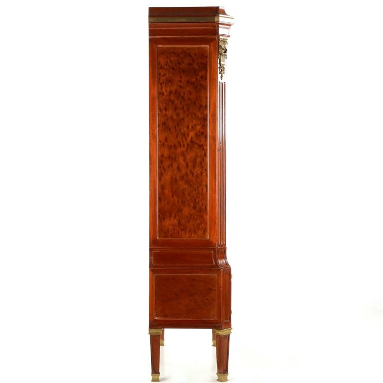 A most unusual and incredibly striking object, this tall case is designed in the Louis XVI taste with a distinct flair of the Neoclassical evident in it's angular form. The facade is evenly distributed with perfect symmetry in the rectangular