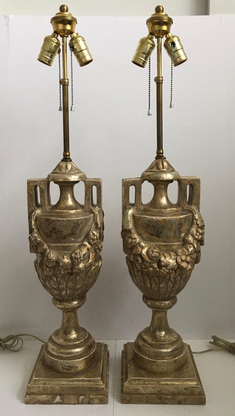 Highly detailed pair of French Neoclassical style silver leaf giltwood urn lamps featuring hand carved draped foliate garland motifs. These Louis XVI style lamps are mounted on marble plinth bases and have adjustable riser finials. Each lamp is