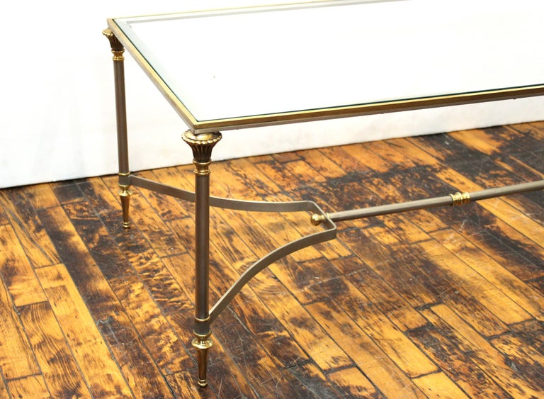 French Neoclassical style Maison Jansen coffee table with stretcher underneath and heavy glass top, made in France during the 1940s, in very good condition with age-appropriate wear and use.