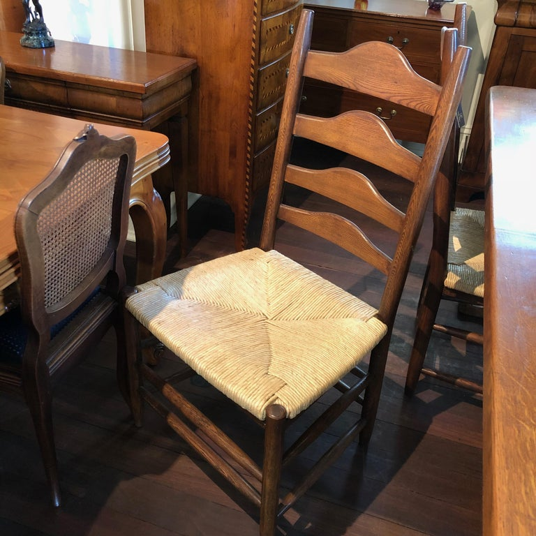 These sensational French oak ladder back dining chairs, feature handcrafted traditional rush seating. They are of utterly grand proportions, making this pair perfect for dining table 'head chairs' or Province styled occasional chairs. They are