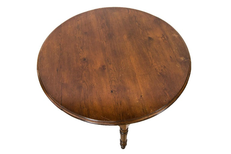 French oak round table has turned and reeded legs with exposed peg construction and a bull nosed molded top. There is one very long, deep drawer.